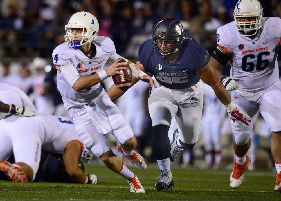 Scott Sommerdorf   |  The Salt Lake Tribune Boise State Broncos QB Brett Rypien (4) is chased out of the pocket and later sacked by Utah State Aggies DE Ricky Ali'ifua (95) during first quarter play. Rypien fumbled, Utah State recovered and later scored a TD to go up 17-3. Utah State led Boise State 17-3 after one quarter of play, Friday, October 15, 2015.