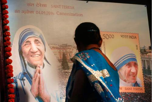 An Indian Christian woman looks at a board displaying a commemorative postage stamp of Mother Teresa during its release function in Mumbai, India, Sunday, Sept. 4, 2016. Pope Francis declared Mother Teresa a saint on Sunday, honoring the tiny nun who cared for the world's most destitute and holding her up as a model for a Catholic Church that goes to the peripheries to find poor, wounded souls. (AP Photo/Rafiq Maqbool)