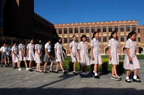 In this Aug. 31, 2016 photo, Chinese students walk in line to attend the opening ceremony of the Haileybury College's Chinese campus in northern China's Tianjin Municipality. International schools from outside China are booming thanks to growing demand from Chinese parents seeking different pathways for their children to college abroad. Top prep schools are opening campuses in China and catering to students who want to go to university in the West. Getting into China's best public high schools can be monumentally difficult and many parents are opting to pay for what they see as a less stressful and more enriching experience at an international school.  (AP Photo/Nomaan Merchant)
