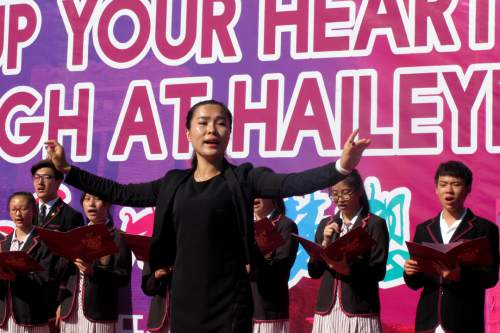 In this Aug. 31, 2016 photo, a lecturer gestures as Chinese students sing a school song during the opening ceremony of the Haileybury College's Chinese campus in northern China's Tianjin Municipality.  International schools from outside China are booming thanks to growing demand from Chinese parents seeking different pathways for their children to college abroad. Top prep schools are opening campuses in China and catering to students who want to go to university in the West. Getting into China's best public high schools can be monumentally difficult and many parents are opting to pay for what they see as a less stressful and more enriching experience at an international school. (AP Photo/Nomaan Merchant)