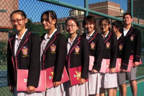 In this Aug. 31, 2016 photo, Chinese students prepare for the opening ceremony of the Haileybury College's Chinese campus in northern China's Tianjin Municipality. International schools from outside China are booming thanks to growing demand from Chinese parents seeking different pathways for their children to college abroad. Top prep schools are opening campuses in China and catering to students who want to go to university in the West. Getting into China's best public high schools can be monumentally difficult and many parents are opting to pay for what they see as a less stressful and more enriching experience at an international school. (AP Photo/Nomaan Merchant)