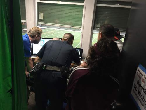 Sgt. Mike Pallotto of the Ventura College police department reviews game footage to determine whether a Mt. St. Antonio College player punched a referee during a community college football game in Ventura, Calif. on Saturday night. The Ventura County Star reports that Mt. St. Antonio freshman offensive linesman Bernard Schirmer was immediately ejected from the game and later arrested on suspicion of battery and taken to Ventura County jail. (Joe Curley/The Ventura County Star via AP)
