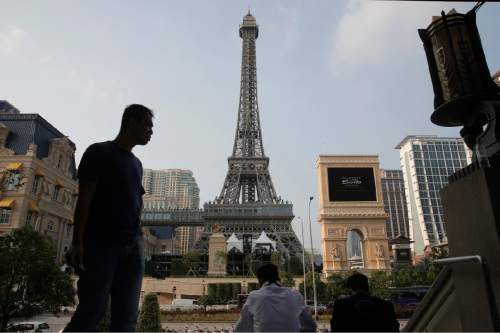 People take a rest in front of a replica of the Eiffel Tower of Parisian Macao, in Macau, Tuesday, Sept. 13, 2016. U.S. billionaire Sheldon Adelson was set to throw open the doors Tuesday to the French-themed Parisian Macao, the mogul's fifth property in the former Portuguese colony. (AP Photo/Kin Cheung)