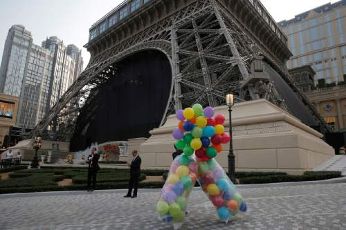 A staff member carries balloons for the opening ceremony in front of a replica of the Eiffel Tower of Parisian Macao in Macau, Tuesday, Sept. 13, 2016. U.S. billionaire Sheldon Adelson was set to throw open the doors Tuesday to the French-themed Parisian Macao, the mogul's fifth property in the former Portuguese colony. (AP Photo/Kin Cheung)