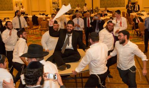 Rick Egan  |  The Salt Lake Tribune  Rabbi Mendy Cohen dances on a spinning table, during a traditional Chassidic wedding celebration at the Grand America, after Cohen was married to Chaya Zippel, Monday, September 12, 2016.