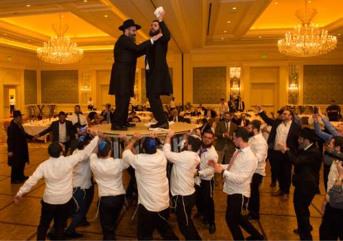 Rick Egan  |  The Salt Lake Tribune  Rabbi Mendy Cohen tosses napkins over the barrier to the women's side as he dances on a table during his traditional Hasidic wedding celebration at the Grand America on Monday, Sept. 12, 2016.