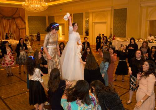 Rick Egan  |  The Salt Lake Tribune  Chaya Zippel tosses napkins over the barrier to the men's side as she dances on a table during her traditional Hasidic wedding celebrating her marriage to Rabbi Mendy Cohen on Monday, Sept. 12, 2016.