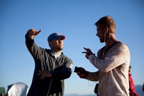 "Director/writer/editor Isaac Halasima (left) talks to actor Landon Henneman during shooting of ""The Last Descent,"" a drama about the attempted 2009 rescue of a trapped climber in Utah's Nutty Putty Cave. Courtesy Excel Entertainment"