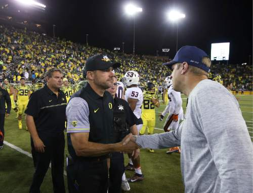 While Oregon defensive coordinator Brady Hoke waits at left, Oregon coach Mark Helfrich and Virginia coach Bronco Mendenhall, right, shake hands after an NCAA college football game Saturday, Sept. 10, 2016, in Eugene, Ore. Oregon won 44 26. (AP Photo/Chris Pietsch)