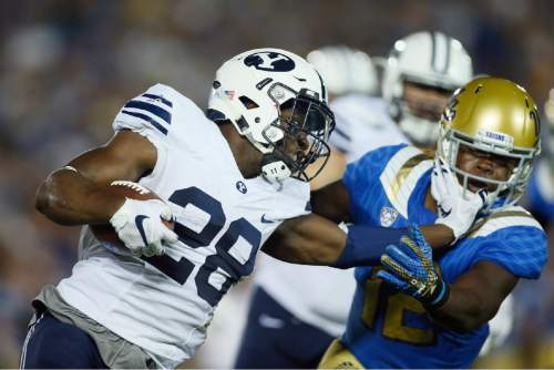 BYU running back Adam Hine stiff-arms UCLA linebacker Jayon Brown during the first half of an NCAA college football game, Saturday, Sept. 19, 2015, in Pasadena, Calif. (AP Photo/Danny Moloshok)