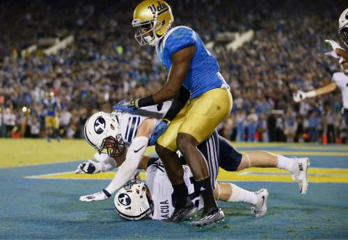 BYU defensive back Michael Wadsworth, middle, jumps on defensive back Kai Nacua, bottom, after Nacua intercepted a pass in the end zone intended for UCLA wide receiver Devin Fuller, top, late in the first half of an NCAA college football game, Saturday, Sept. 19, 2015, in Pasadena, Calif. (AP Photo/Danny Moloshok)