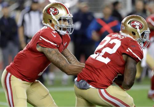 San Francisco 49ers quarterback Colin Kaepernick, left, hands off to running back Mike Davis (22) during the second half of an NFL football game against the Los Angeles Rams in Santa Clara, Calif., Monday, Sept. 12, 2016. The 49ers won 28-0. (AP Photo/Marcio Jose Sanchez)