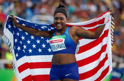 In this photo released by the IOC, Deja Young, of the United States, poses for a photo with her country's national flag after winning the gold medal in the women's 200-meter - T47 final athletics event, at the Olympic Stadium, during the Paralympic Games in Rio de Janeiro, Brazil, Friday, Sept. 16, 2016. (Simon Bruty/OIS, IOC via AP)