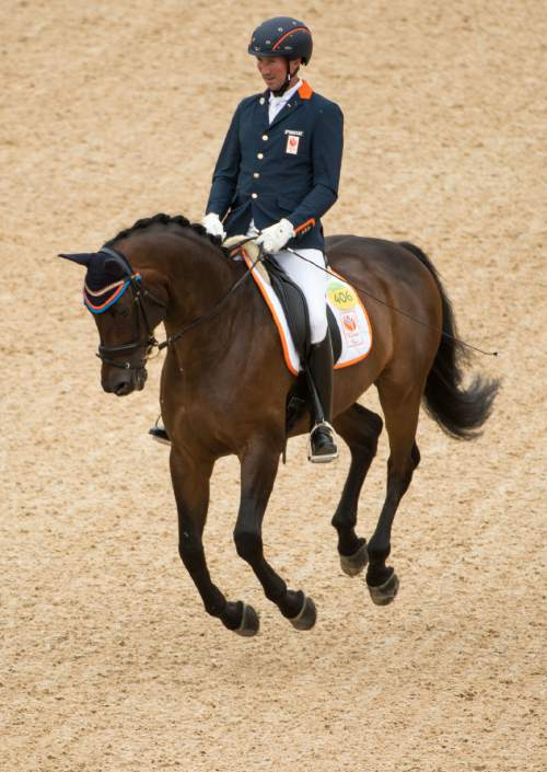 In this photo released by the IOC, bronze medallist Frank Hosmar, of the Netherlands, on Alphavilleon, competes in the individual freestyle test grade IV, part of the Equestrian Dressage event at the Olympic Equestrian Center, during the Paralympic Games in Rio de Janeiro, Brazil, Friday, Sept. 16, 2016. (Thomas Lovelock/OIS, IOC via AP)