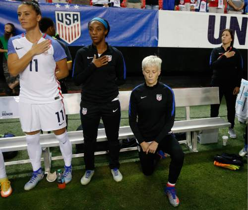 USA's Megan Rapinoe, right, kneels next to teammates Ali Krieger (11) and Crystal Dunn (16) as the US national anthem is played before an exhibition soccer match against Netherlands, Sunday, Sept. 18, 2016, in Atlanta. (AP Photo/John Bazemore)