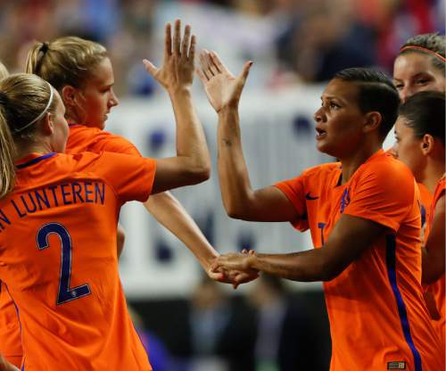 Netherlands' Shanice van de Sanden (7), right, celebrates with Vivianne Miedema (9) and Desiree van Lunteren (2) after scoring a goal in the first half of an exhibition soccer match against the USA, Sunday, Sept. 18, 2016, in Atlanta. (AP Photo/John Bazemore)