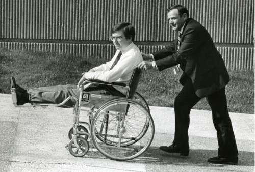 Tribune file photo Mark Hofmann being pushed in wheel chair by his father.