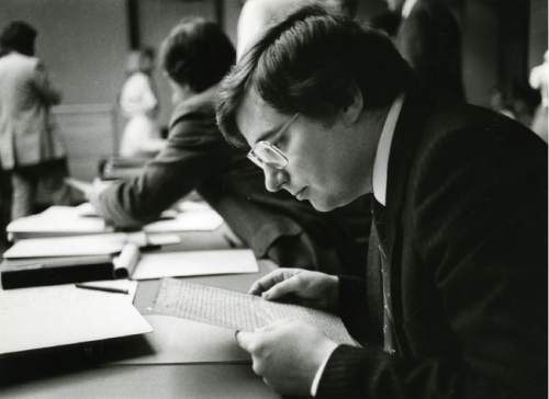 "Tribune file photo Mark Hofmann peruses the ""White Salamander Letter"" during a court hearing."
