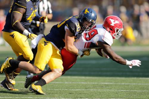 FILE - In this Sept. 10, 2016, file photo, West Virginia linebacker Justin Arndt (30) tackles Youngstown State running back Martin Ruiz (29) during the second half of an NCAA college football game, in Morgantown, W.Va. West Virginia has nine new starters on defense and has allowed an average of 434 yards per game. The Mountaineers don't play this Saturday and are using the extra time to prepare for a Sept. 24 game against BYU in Landover, Maryland. (AP Photo/Raymond Thompson, File)