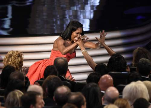 """Regina King celebrates her win for the award for outstanding supporting actress in a limited series or movie for """"American Crime"""" at the 68th Primetime Emmy Awards on Sunday, Sept. 18, 2016, at the Microsoft Theater in Los Angeles. (Photo by Chris Pizzello/Invision/AP)"""