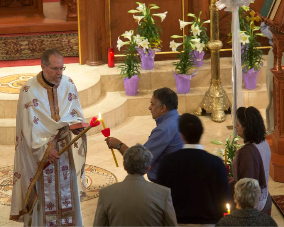 Steve Griffin     The Salt Lake Tribune  Fr. Matthew Gilbert lights candles during Easter Sunday service for the Greek Orthodox Church at the Holy Trinity Greek Orthodox Cathedral in Salt Lake City, Sunday, April 12, 2015.