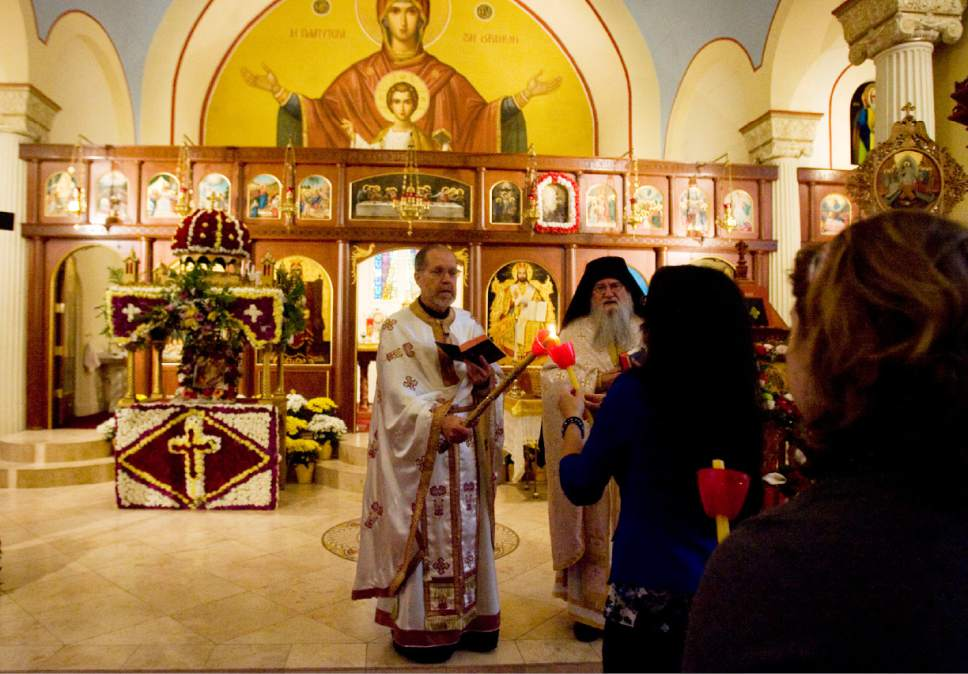    Tribune File Photo  Father Matthew Gilbert lights the candles of parishioners during the Agape Vespers service, which culminates the end of Holy Week festivities for the Orthodox Christian faith, at the Holy Trinity Cathedral in Salt Lake City on May 5, 2013. Lighting the candles during the service symbolizes the light of Christ.