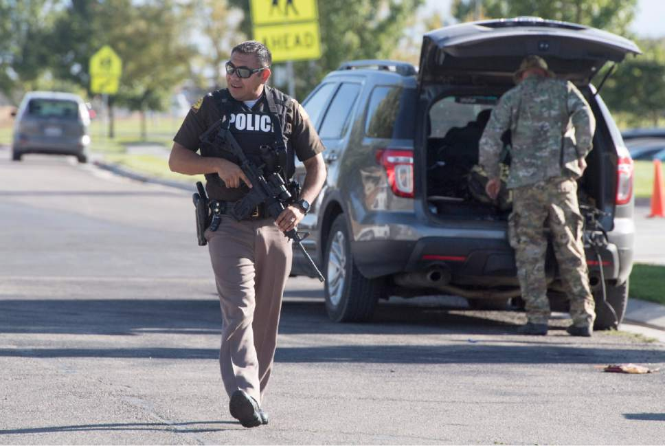 Rick Egan  |  The Salt Lake Tribune  Police block off the road in front of Eagle Valley Elementary School in Eagle Mountain. The school was evacuated after a masked man entered the school on Monday, Sept. 19, 2016.