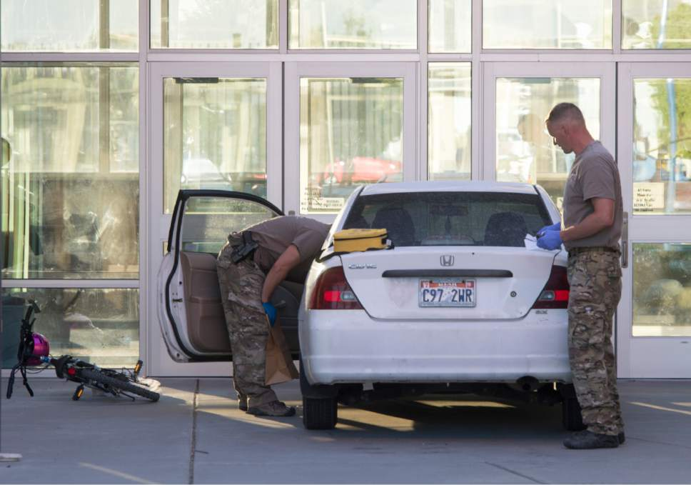 Rick Egan  |  The Salt Lake Tribune Police check out the suspect's car at Eagle Valley Elementary School in Eagle Mountain in September. The school was evacuated after a masked man entered the school and claimed the car contained explosives.