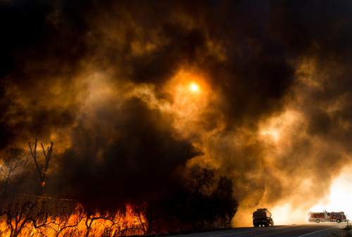 FILE - In this Aug. 17, 2016 file photo, firefighters battle a wildfire as it crosses Cajon Boulevard in Keenbrook, Calif. This past summer's weather was relentless and hellish, crowded with the type of record-smashing extremes that scientists have long warned about. The season ends Wednesday, Sept. 21, 2016, and not a moment too soon. Summer featured floods that killed hundreds of people and caused more than $50 billion in losses around the globe, from Louisiana and West Virginia to China, India, Europe and the Sudan. Meanwhile, droughts parched croplands and wildfires burned from California to Canada to China and India. Toss in unrelenting record heat. (AP Photo/Noah Berger, File)