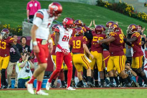 Chris Detrick  |  The Salt Lake Tribune Utah Utes quarterback Travis Wilson (7) and Utah Utes wide receiver Tyrone Smith (81) walk off of the field as USC Trojans celebrate a interception touchdown by USC Trojans linebacker Cameron Smith (35) during the game at the Los Angeles Memorial Coliseum Saturday October 24, 2015.