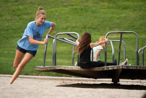 Rick Egan     The Salt Lake Tribune  Kids play on the merry-go-round at Lindsey Gardens, Sunday, July 19, 2015. There is a plan to renovate the Lindsey Gardens playground and get rid of the classic metal merry-go-round. Residents are organizing to save it. Wednesday, September 14, 2016.