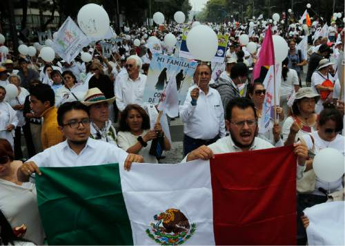 Demonstrators hold up a Mexican national flag during a march organized by representatives of the National Front for the Family, in Mexico City, Saturday, Sept. 24, 2016. Dueling marches, in support and against Mexican President Enrique Pena Nieto's push to legalize same-sex marriage, gathered at the Angel of Independence monument. The two sides were kept apart Saturday by hundreds of police and barriers erected around the city's iconic monument. (AP Photo/Marco Ugarte)