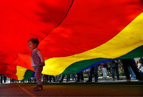 A girl walks under a rainbow flag during a gay rights march along Reforma Avenue, in Mexico City, Saturday, Sept. 24, 2016. Dueling marches, in support and against Mexican President Enrique Pena Nieto's push to legalize same-sex marriage, gathered at the Angel of Independence monument. The two sides were kept apart Saturday by hundreds of police and barriers erected around the city's iconic monument. (AP Photo/Marco Ugarte)