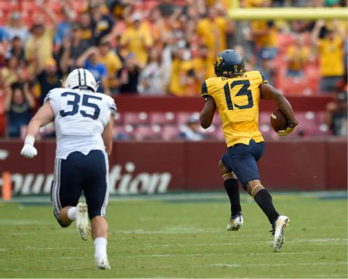West Virginia cornerback Rasul Douglas (13) runs toward the end zone with the ball after he intercepted it as Brigham Young running back Brayden El-Bakri (35) pursues during the first half of an NCAA college football game , Saturday, Sept. 24, 2016, in Landover, Md. Douglas scored a touchdown on the play. (AP Photo/Nick Wass)