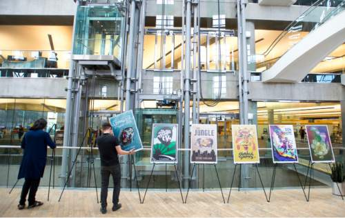 """Steve Griffin / The Salt Lake Tribune   Andrew Shaw and Tommy Hamby install the """"Reconsidering the Classics"""" exhibit at the Salt Lake City Main Library in Salt Lake City on Thursday, Sept. 22, 2016.  The exhibit features new artwork for classic books, including Shakespeare plays. It's part of the Utah Book Festival and Library's partnership that is also hosting a copy of Shakespeare's First Folio."""