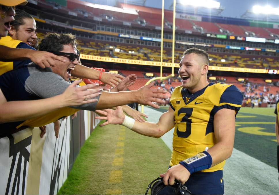 West Virginia quarterback Skyler Howard (3) celebrates with fans after an NCAA college football game against BYU, Saturday, Sept. 24, 2016, in Landover, Md. (AP Photo/Nick Wass)