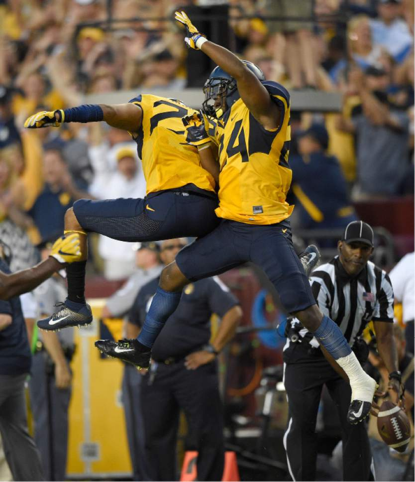 West Virginia cornerback Maurice Fleming, right, celebrates with safety Jarrod Harper, left, after intercepting the ball against BYU late in the second half of an NCAA college football game, Saturday, Sept. 24, 2016, in Landover, Md. (AP Photo/Nick Wass)