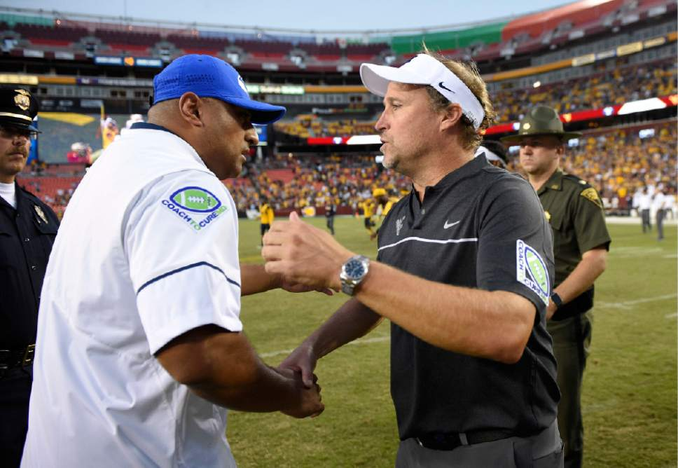 West Virginia head coach Dana Holgorsen, right, shakes hands with BYU head coach Kalani Sitake, left, after an NCAA college football game, Saturday, Sept. 24, 2016, in Landover, Md. (AP Photo/Nick Wass)
