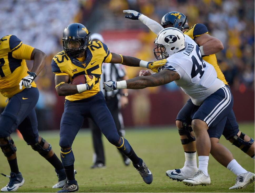 West Virginia running back Justin Crawford (25) runs past BYU defensive lineman Tomasi Laulile (48) during the second half of an NCAA college football game, Saturday, Sept. 24, 2016, in Landover, Md. (AP Photo/Nick Wass)