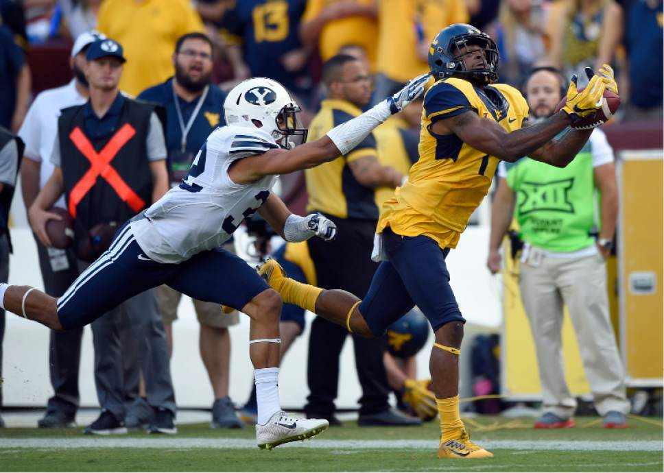 West Virginia wide receiver Shelton Gibson , right, makes a catch against BYU defensive back Chris Wilcox, left, during the second half of an NCAA college football game, Saturday, Sept. 24, 2016, in Landover, Md. (AP Photo/Nick Wass)