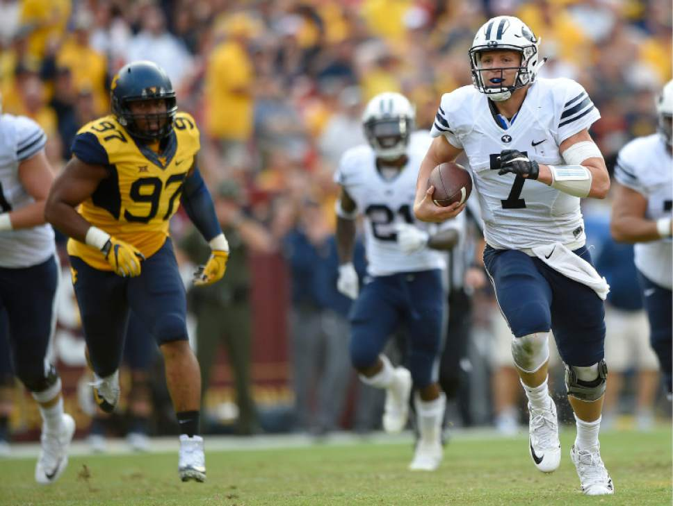 Brigham Young quarterback Taysom Hill (7) scrambles upfield as West Virginia defensive lineman Noble Nwachukwu (97) pursues during the second half of an NCAA college football game, Saturday, Sept. 24, 2016, in Landover, Md. (AP Photo/Nick Wass)