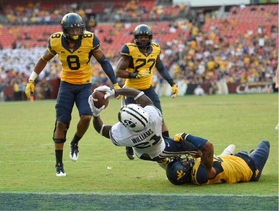 BYU running back Jamaal Williams (21) dives into the end zone for a touchdown during the second half of an NCAA college football game against West Virginia safety Jarrod Harper, right bottom, Kyzir White (8), and Sean Walters (27), Saturday, Sept. 24, 2016, in Landover, Md. (AP Photo/Nick Wass)