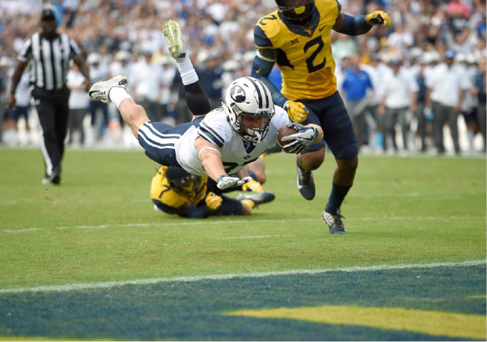 Brigham Young wide receiver Mitchell Juergens, left, dives for the end zone for a touchdown past West Virginia safety Jeremy Tyler (2) during the first half of an NCAA college football game, Saturday, Sept. 24, 2016, in Landover, Md. (AP Photo/Nick Wass)