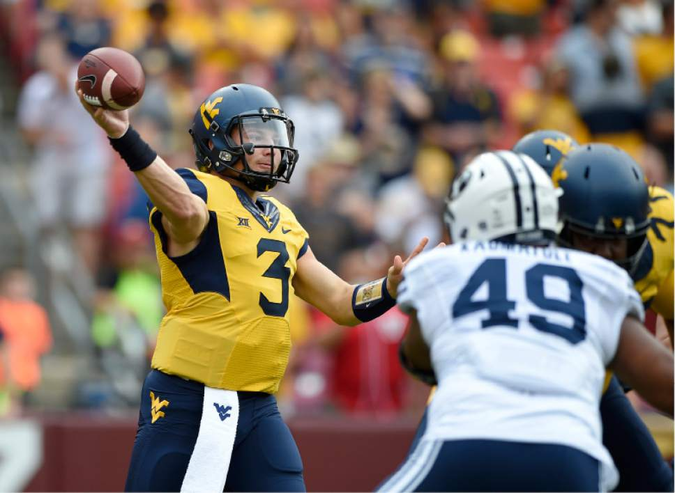 West Virginia quarterback Skyler Howard (3) passes while pressured by BYU defensive lineman Moses Kaumatule (49) during the first half of an NCAA college football game, Saturday, Sept. 24, 2016, in Landover, Md. (AP Photo/Nick Wass)