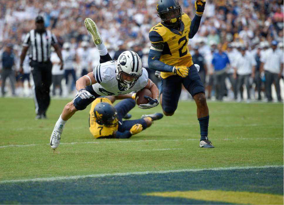 Brigham Young wide receiver Mitchell Juergens, left, dives for the end zone for the touchdown past West Virginia safety Jeremy Tyler (2) during the first half of an NCAA college football game, Saturday, Sept. 24, 2016, in Landover, Md. (AP Photo/Nick Wass)