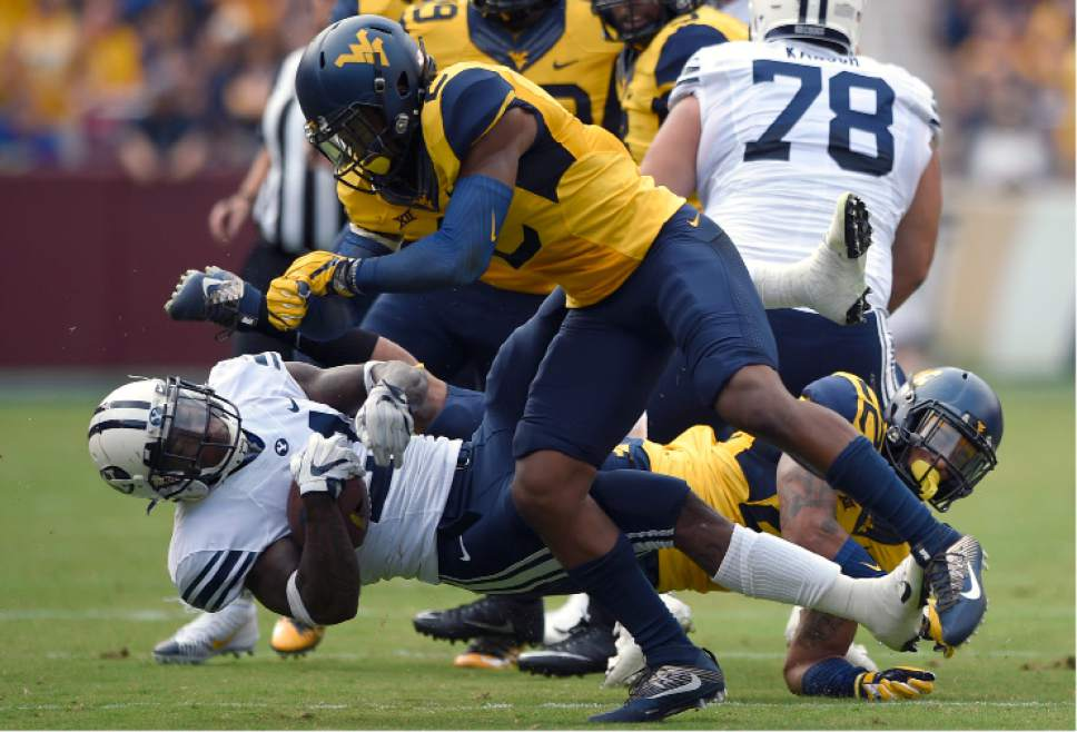 BYU running back Jamaal Williams, bottom, is knocked down by West Virginia safety Jeremy Tyler (2) during the first half of an NCAA college football game, Saturday, Sept. 24, 2016, in Landover, Md. (AP Photo/Nick Wass)