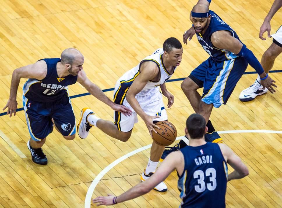Chris Detrick  |  The Salt Lake Tribune Utah Jazz guard Dante Exum (11) runs past Memphis Grizzlies guard Nick Calathes (12) and Memphis Grizzlies guard Vince Carter (15) during the game at EnergySolutions Arena Friday April 10, 2015.