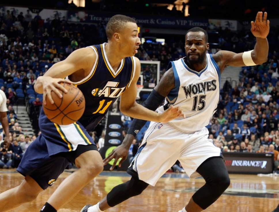 Utah Jazz's Dante Exum, left, of Australia, drives around Minnesota Timberwolves' Shabazz Muhammad in the first quarter of an NBA basketball game, Saturday, Jan. 3, 2015, in Minneapolis. (AP Photo/Jim Mone)