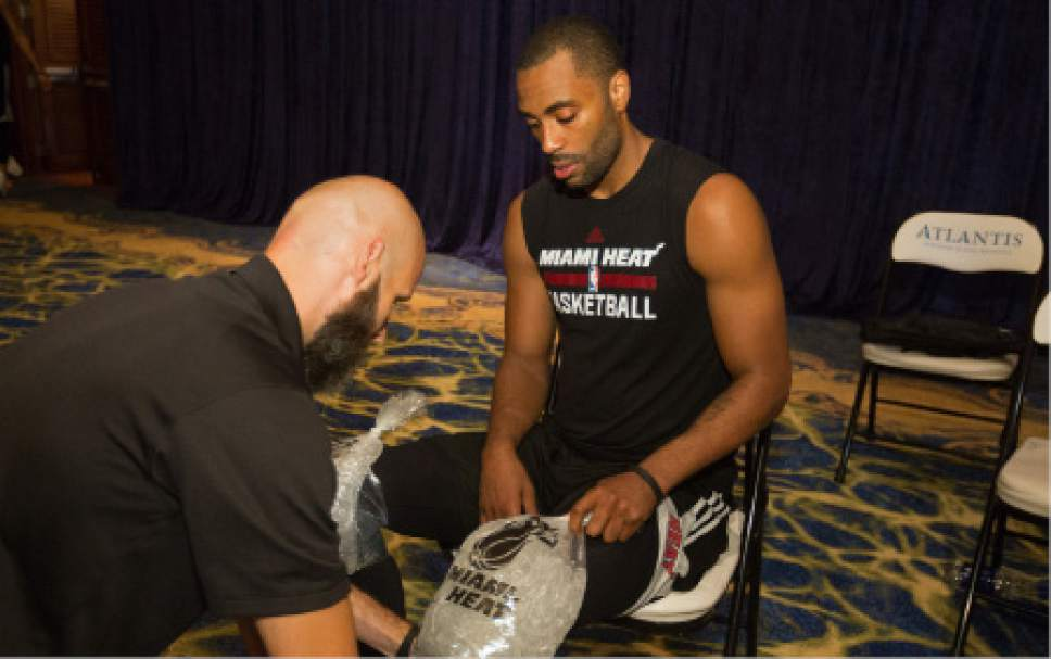 Miami Heat's Wayne Ellington applies ice to his knees during training camp in Nassau, Bahamas, Tuesday, Sept. 27, 2016. The team arrived in the Bahamas Monday for a week-long training session at Atlantis, Paradise Island. (AP Photo/Tim Aylen)