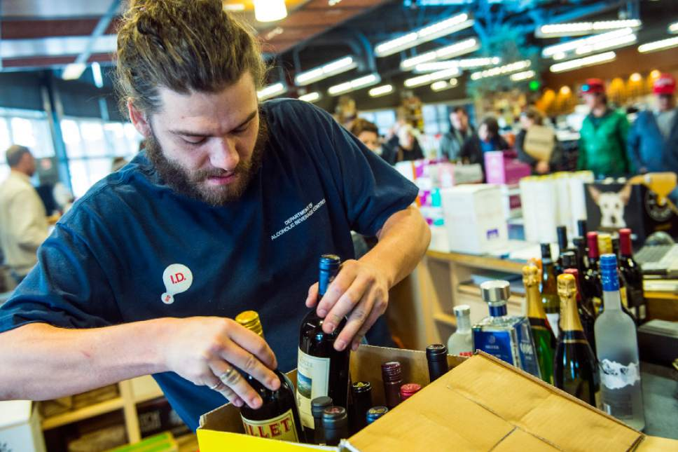 Tribune file photo An employee packs wine and liquor for a customer at the Utah Wine Store in Salt Lake City in 2015.